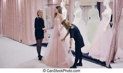 Pretty girl chooses a prom dress in shop - girl chooses a...
