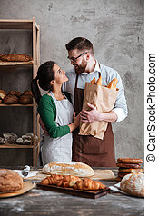 Vertical image of happy bakers in bakery - Vertical image of...