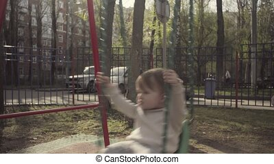 Mom swinging a kid on a swing in the courtyard