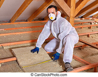 Man laying thermal insulation - Man installing thermal...