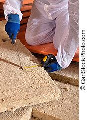 Man cutting rockwool panel to fit in thermal insulation...