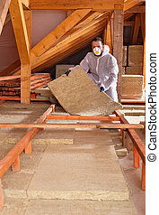 Man places rockwool thermal insulation between wooden scaffolding