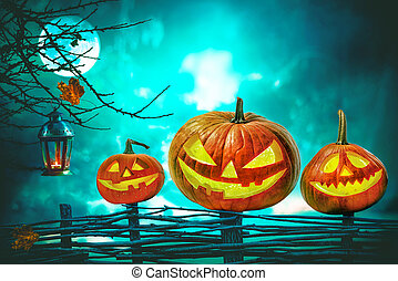 Halloween pumpkins in front of nightly spooky forest