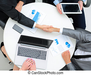 Successful businesspeople shaking hands in a modern office -...