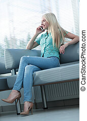 Photo of a girl talking on the phone and looking out the window