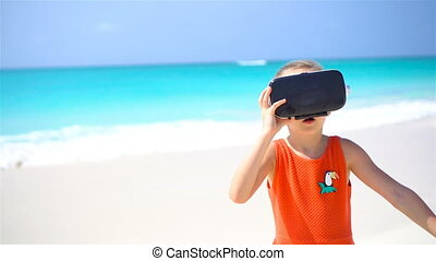 Cute little child girl using VR virtual reality goggles....