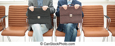 two businessmen sitting in a chairs with a portfolio in...