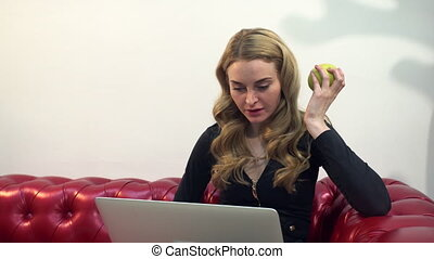 Beautiful young blonde woman on red sofa using laptop and eating a green apple in living room.