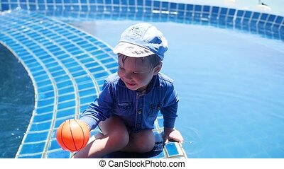 Little child is playing ball in the pool. Sports in the open...