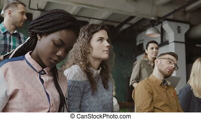 Group of multiethnic people sit at loft office and listen...