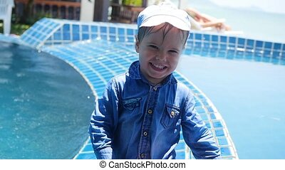 A small child sits next to the pool . Sports outdoors. - A...