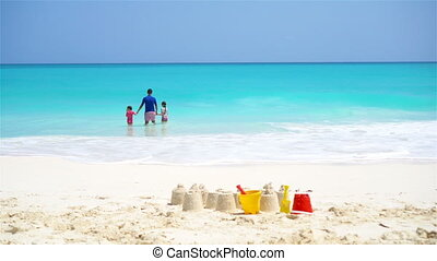 Sandcastle at white beach with plastic kids toys and family in the sea background