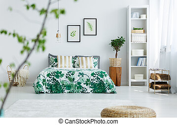 White bedroom with bookcase, plant, double bed and trendy...
