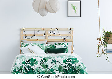 White bedroom with wooden bed, swing and string lights