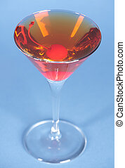 Rob Roy cocktail on blue background in martini glass