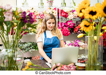 Flower shop owner using a computer