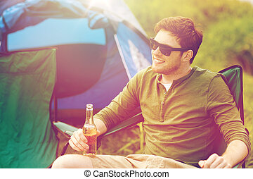 happy young man drinking beer at campsite tent - camping,...