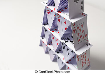 house of playing cards over white background - casino,...