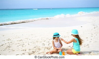 Kids applying sun cream to each other on the beach. The...