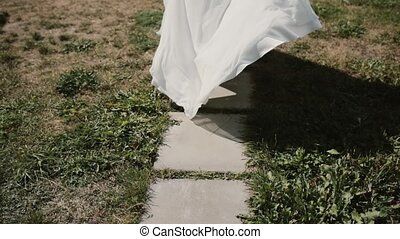 Close-up view of young woman in white dress running at park....