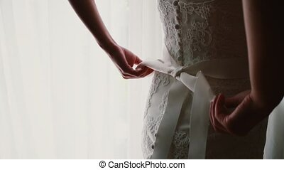 Close-up view of young bride makes a bow on her wedding dress. Woman standing near window and getting ready for ceremony