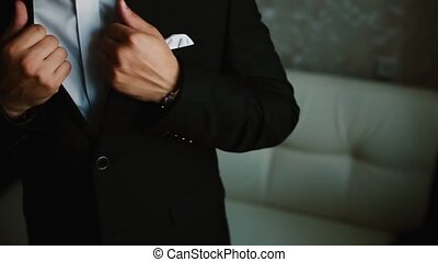 Close-up view of young businessman puts on the black tuxedo....