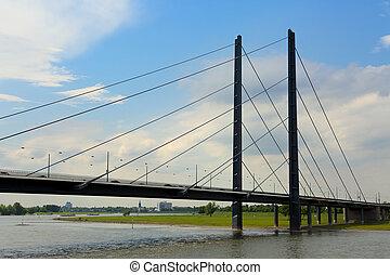 Long metal bridge above the Rhine river in Dusseldorf,...