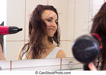 Young woman drying her hair in bathroom - Young charming...