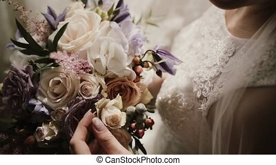 Close-up view of young bright with wedding bouquet. Woman...