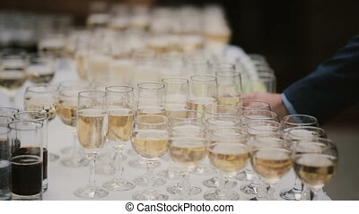 A lot of glasses of champagne on the table, a man in costume takes one serving of alcohol. Luxury business meeting.