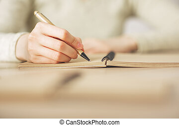 Female writing in notepad - Close up of female hands writing...