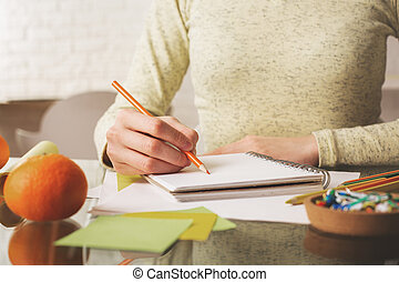 Girl writing in spiral notepad - Close up and front view of...