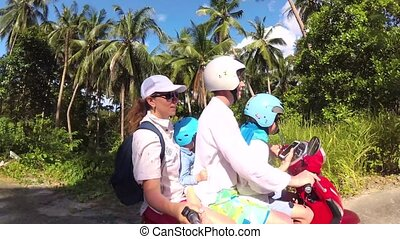 happy family riding a motorcycle in the tropics. A bright Sunny day. PHANGAN, THAILAND