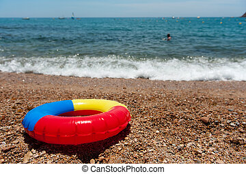 Toy life preserver in colors at the beach