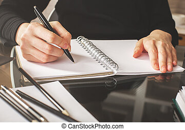 Woman writing in spiral notepad - Close up and front view of...