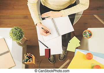 Woman writing in notepad top - Top view of woman writing in...