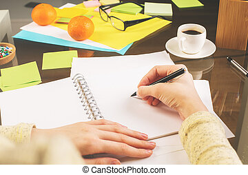 Businesswoman writing in notepad - Close up of...