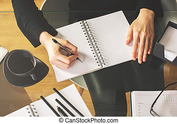 Female writing in spiral notepad top - Top view of female...