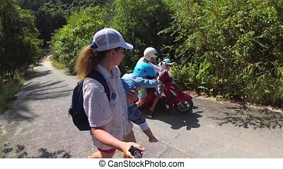 Family with two children traveling on motobike. A bright...