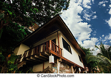 Bungalows among tropical trees. Staircase house on stilts...
