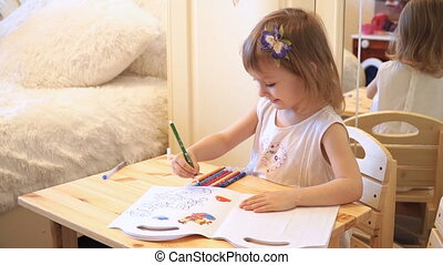 Active little preschool age child, cute toddler girl with blonde curly hair, drawing picture on paper using colorful pencils and felt-tip pens, sitting at wooden table indoors at home or kindergarten