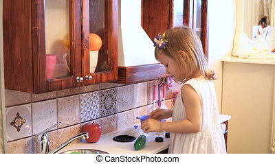 Active little preschool age child, cute toddler girl with blonde curly hair, shows playing kitchen, made of wood, plays in the kitchen