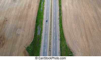 Aerial drone shot of empty motorway. Car driving through the...