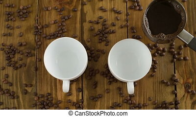 Pouring coffee into two cups on a wooden table
