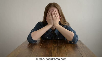 Depressed woman crying at a wooden table - Depressed woman...