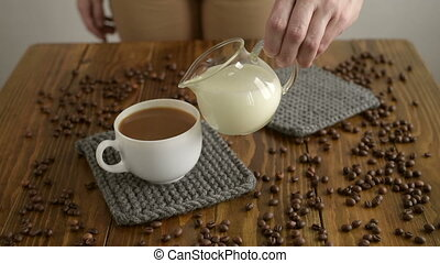 Pouring milk into a cup of coffee - Woman pouring milk into...