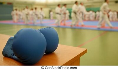 Blue karate gloves on tatami during training, de-focused,...