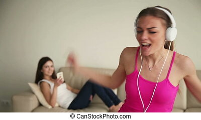 Young woman alone at home singing and having fun - Two happy...