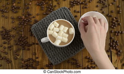 Putting marsh mallows into coffee - Putting marsh mallows...