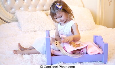 An active little preschool child, a pretty little girl with a blond curly hair, plays with her dolls, puts them to sleep in